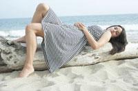 ビーチの木の上に寝る女性