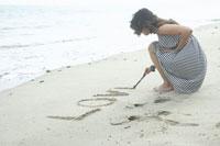 砂浜に字を書く女性