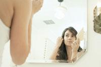 鏡の前で髪を梳かす女性