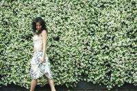 花壁沿いに散歩する女性