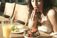 屋外で朝食をとる女性