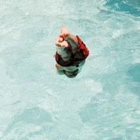 プールに飛び込む瞬間の少年