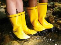 川に入る長靴をはいた少年2人の足