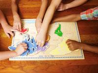 地球パズルをする子供たちの手