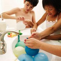 洗面台で水風船を作る少年少女3人