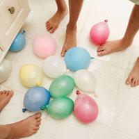 床に置かれた水風船と子供の足