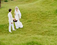 草原で花篭を持つ白人新郎新婦