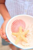 ボールに入れた貝殻を持つ女の子