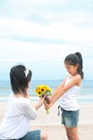 海岸でひまわりを母親に渡す娘