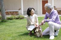 庭で犬と遊ぶシニアカップル 24020000143| 写真素材・ストックフォト・画像・イラスト素材|アマナイメージズ