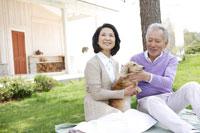 庭に犬と一緒に座り微笑むシニアカップル 24020000154| 写真素材・ストックフォト・画像・イラスト素材|アマナイメージズ