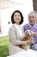 庭に犬と一緒に座り微笑むシニアカップル