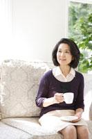 ソファに座りコーヒーを飲むシニア女性