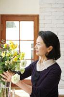 花瓶に花を活けるシニア女性