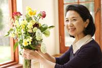 花瓶に花を活けるシニア女性 24020000190| 写真素材・ストックフォト・画像・イラスト素材|アマナイメージズ