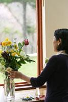 花を活けながら外を見るシニア女性 24020000273| 写真素材・ストックフォト・画像・イラスト素材|アマナイメージズ