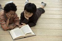 本を一緒に読む少年2人