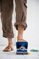 缶をつぶす男性の足元