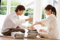 新聞を束ねる男性と女性