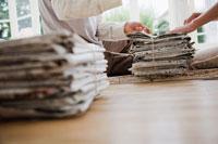 新聞を束ねる男性と女性の手元
