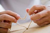 ダンボールに紐をかける男性の手元