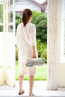 新聞の束を持つ女性