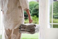 新聞の束を持つ女性の手元