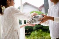 新聞の束を男性に渡す女性