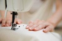 ミシンで布を縫う女性の手元