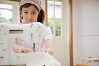 ミシンで布を縫う女性