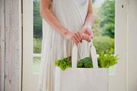 野菜の入ったエコバッグを持つ女性の手元