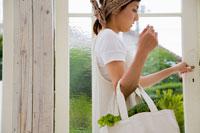 野菜の入ったエコバッグを持つ女性