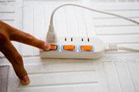 節電コンセントの電源をオフにする男性の手元