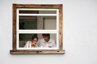 窓際でキャンドルを灯す男性と女性