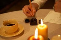 テーブルで手紙を書く男性の手元