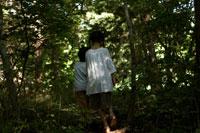森の中を歩く少年少女の後ろ姿