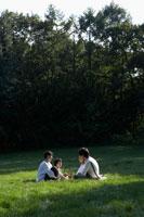 芝生の上に座り談笑する家族4人