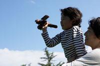 木製飛行機を飛ばす息子と父