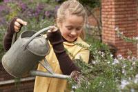 ジョウロで花に水をあげる少女