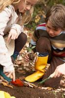 土を掘る少年少女2人 24024000270| 写真素材・ストックフォト・画像・イラスト素材|アマナイメージズ