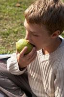洋ナシを食べる少年