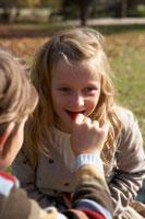 少年にイチゴを食べさせてもらう少女