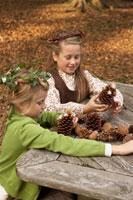 木の実で遊ぶ少女2人 24024000349  写真素材・ストックフォト・画像・イラスト素材 アマナイメージズ