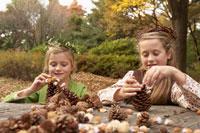 木の実で遊ぶ少女2人 24024000350  写真素材・ストックフォト・画像・イラスト素材 アマナイメージズ