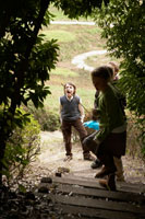 木のアーチの奥に佇む少年少女3人 24024000363| 写真素材・ストックフォト・画像・イラスト素材|アマナイメージズ