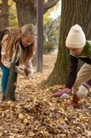 落ち葉を集める少年少女2人