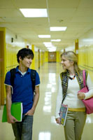 廊下で歩きながら話す2人の学生