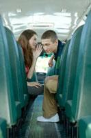 スクールバスで話す学生男女