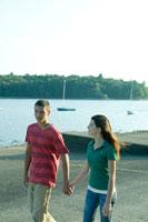 湖畔で手を繋ぎ散歩する男女学生