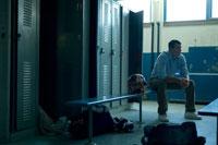 ロッカー室のベンチに座る学生